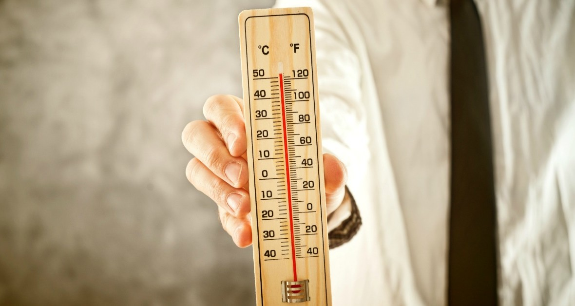 Businessman holding thermometer, measuring high temperatures. Conceptual image.